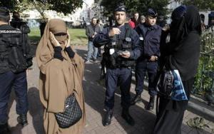 French police and gendarmes check identity cards of women wearing full-face veils, or niqab, as they arrived to demonstrate after calls on the internet by Islamic groups to protest over an anti-Islam video, in Lille