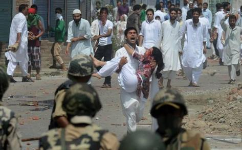 a-kashmir-man-carries-an-injured-women-during-a-clash-between-protesters-and-indian-forcess-on-eid-day