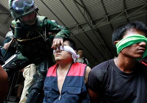 "Thai army soldier stands guard over handcuffed detainees during an operation to evict anti-government ""red shirt"" protesters from their encampment in Bangkok"